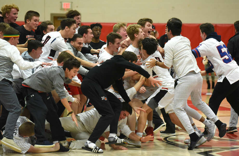 The New Canaan Rams and some of their fans celebrate on the court after beating Stamford 52-49 at New Canaan High School on Thursday, Jan. 10. — Dave Stewart/Hearst Connecticut Media