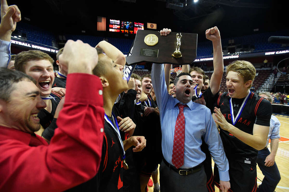 New Canaan head coach Danny Melzer holds up the championship plaque with his players after defeating Granby 55-39 in the CIAC Div. IV final at Mohegan Sun Arena on Saturday, March 16. - Matt Brown/Hearst Connecticut Media