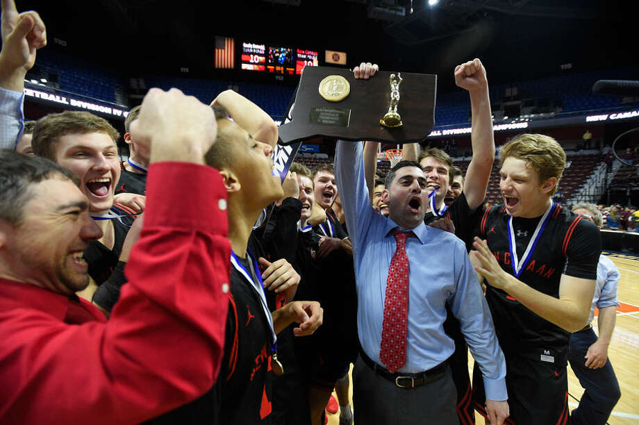 New Canaan head coach Danny Melzer holds up the championship plaque with his players after defeating Granby 55-39 in the CIAC Div. IV final at Mohegan Sun Arena on Saturday, March 16. — Matt Brown/Hearst Connecticut Media / Stamford Advocate