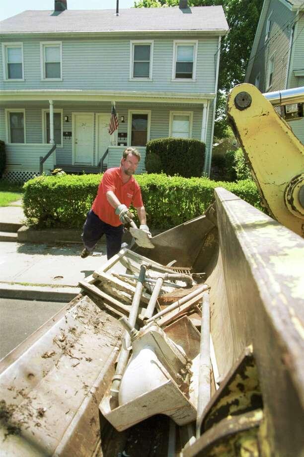 Sean McNamara loads up trash on Cove Road as part of the city's bulk waste pick-up. Photo: Hearst Connecticut Media File / SCNI
