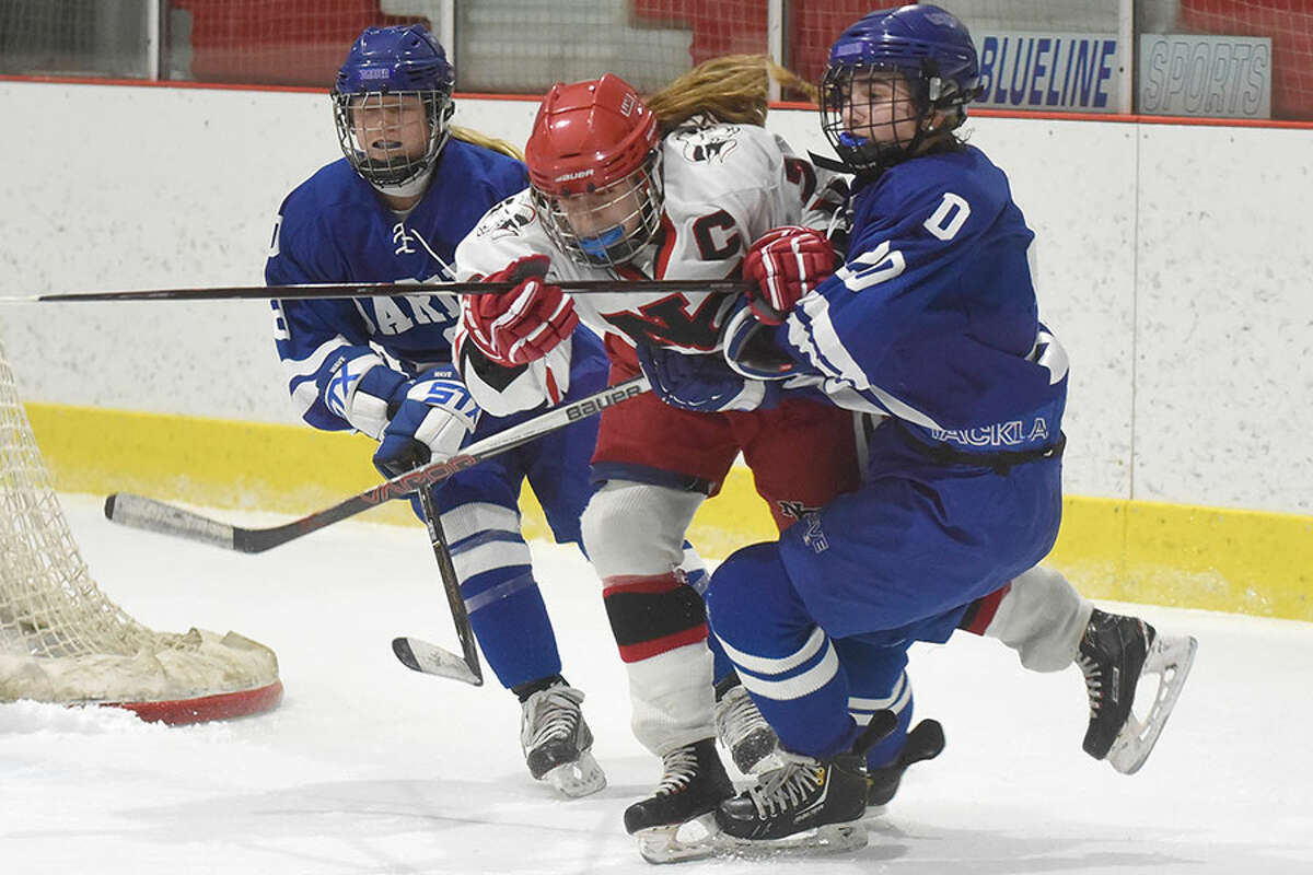 New Canaan's Jess Eccleston (7) and Darien's Nelle Kniffin (20) and Evelyn Hidy (8) mix it up during a girls ice hockey game at the Darien Ice House on Saturday, Jan. 26. - Dave Stewart/Hearst Connecticut Media photo