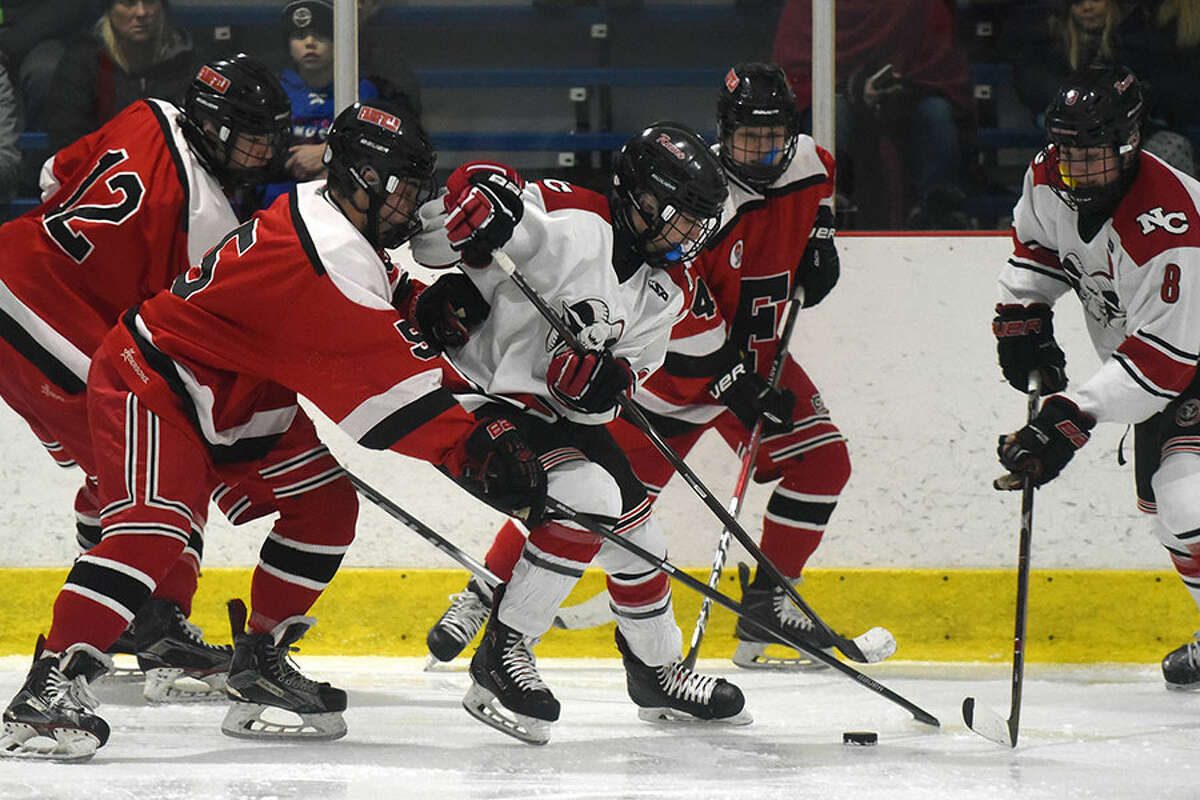 New Canaan's Brendan Knightly (7) plays the puck in traffic, with teammate Jack O'Hare (8) and Fairfield's Kevin Quinn (5), Brady Pomer (12) and Bobby Winter (4) also in pursuit during a boys ice hockey game at the Darien Ice House on Monday, Jan. 21. - Dave Stewart/Hearst Connecticut Media photo