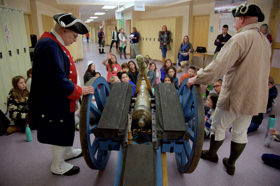 Angus MacDonald, left, and Tom Angels talk to students about the cannon at the Colonial Era re-enactment at Saxe Middle School on Friday, March, 1. Jarret Liotta / Hearst Connecticut Media / Connecticut Post