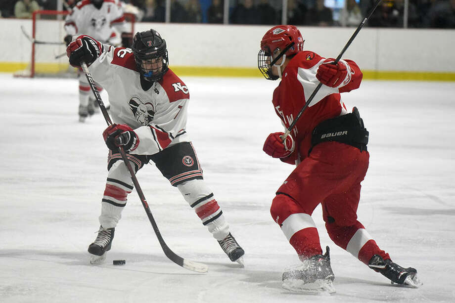 New Canaan's Brendan Knightly (7) and Greenwich's Dylan Madden (11) battle for the puck during the first round of the CIAC Div. I tournament on Tuesday, March 5, at the Darien Ice House. — Dave Stewart/Hearst Connecticut Media