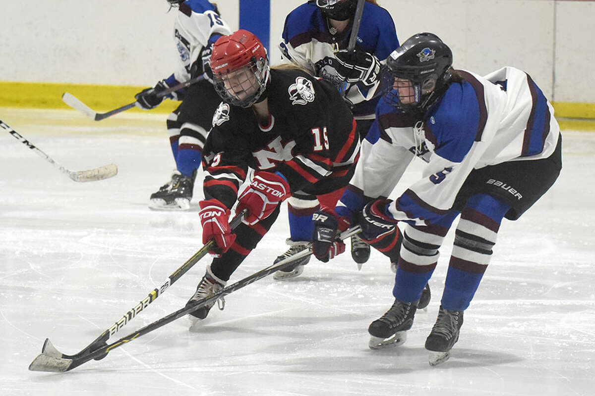 New Canaan's Caitlin Tully (15) and Suffield's Sydney Eitel (5) battle for the puck during the state quarterfinals Saturday at the Darien Ice House. - Dave Stewart Hearst Connecticut Media