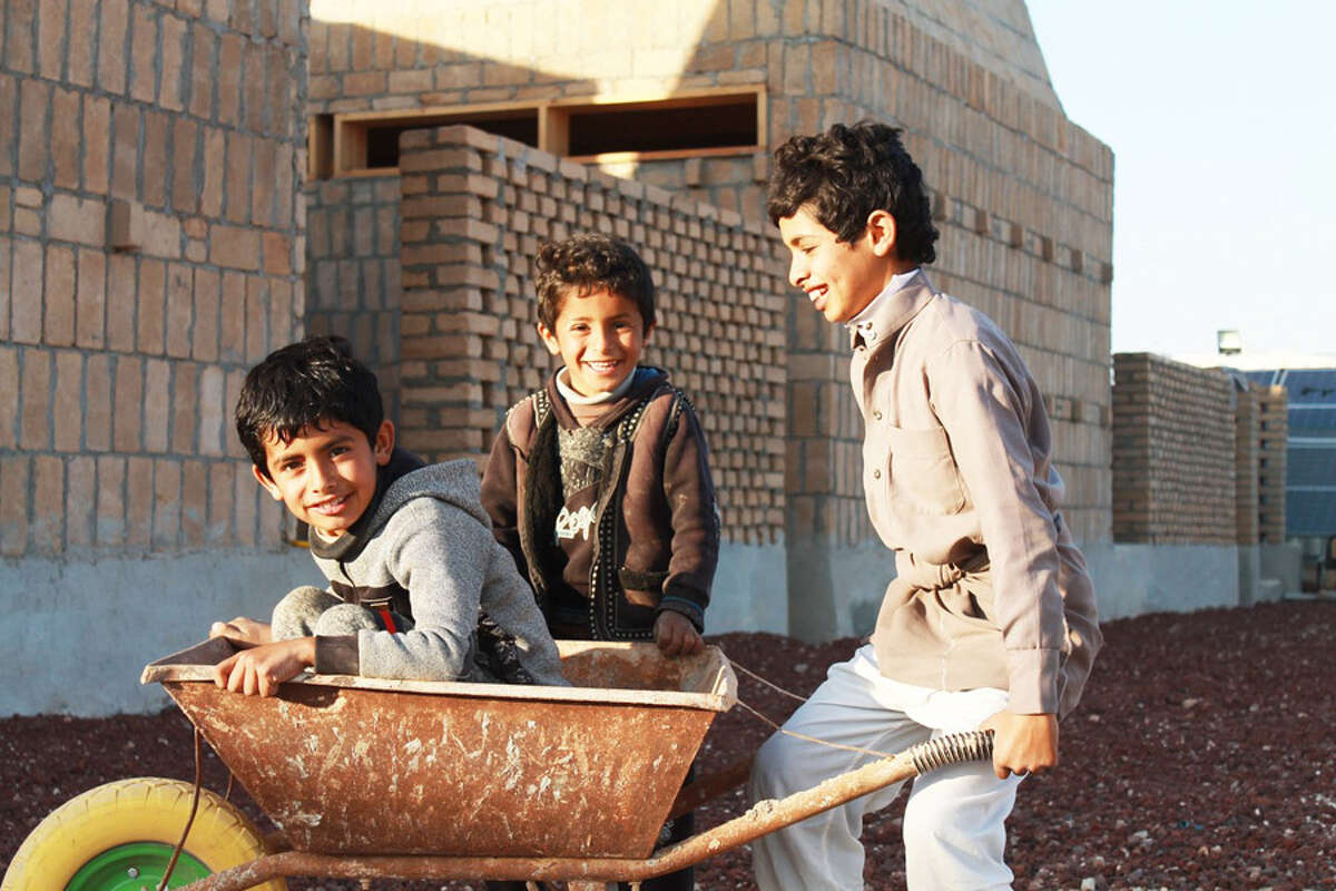 Refugee children play on the grounds of the new school that is being built byBlossomHill Fellow Lexi Shereshewsky in Azraq, Jordan. Parents of these children have been hired as construction workers to help build the school.