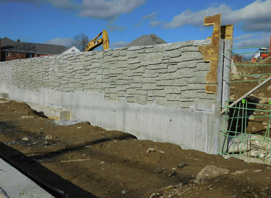 A view of a concrete wall built along Park Street as part of the Merritt Village residential project being constructed.