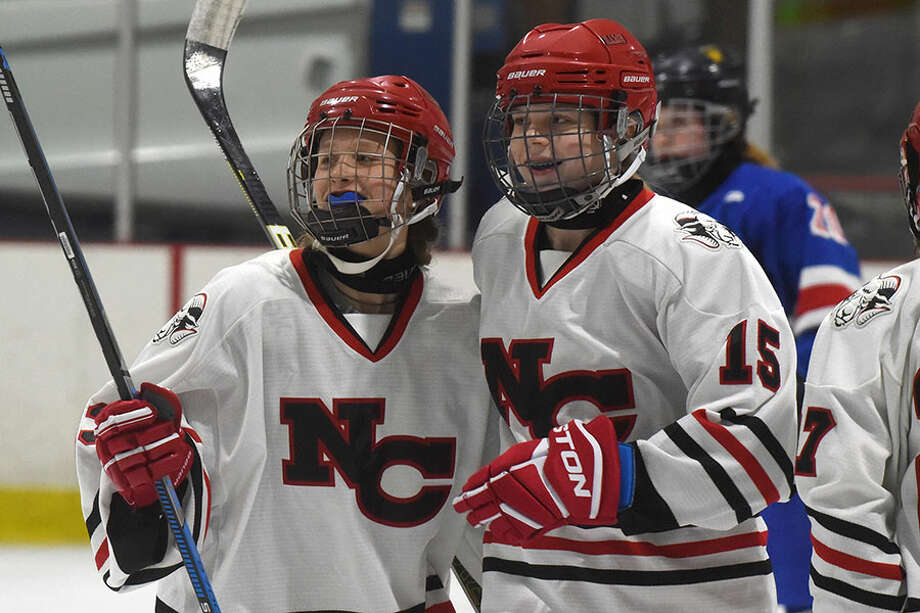 New Canaan freshmen Jade Lowe (left) and Caitlin Tully (15) celebrate Lowe's second-period goal during the FCIAC girls hockey semifinals at the Darien Ice House on Thursday, Feb. 21. — Dave Stewart/Hearst Connecticut Media photo