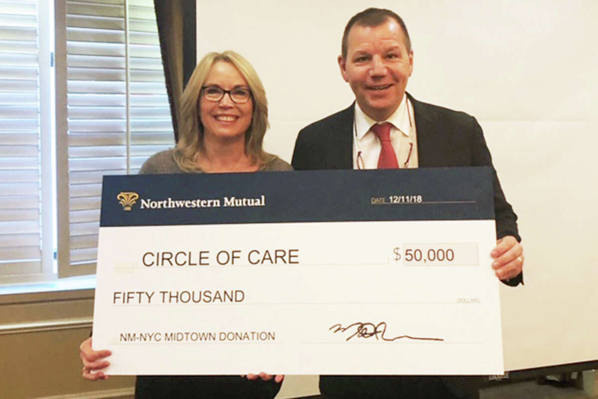 The Circle of Care's Liz Salguero accepts a check for $50,000 from Matt Russo. Russo's Northwestern Mutual NYC Midtown office was awarded the Northwestern Mutual Foundation's 2019 Childhood Cancer Impact Award and donated the funds to the Circle of Care.
