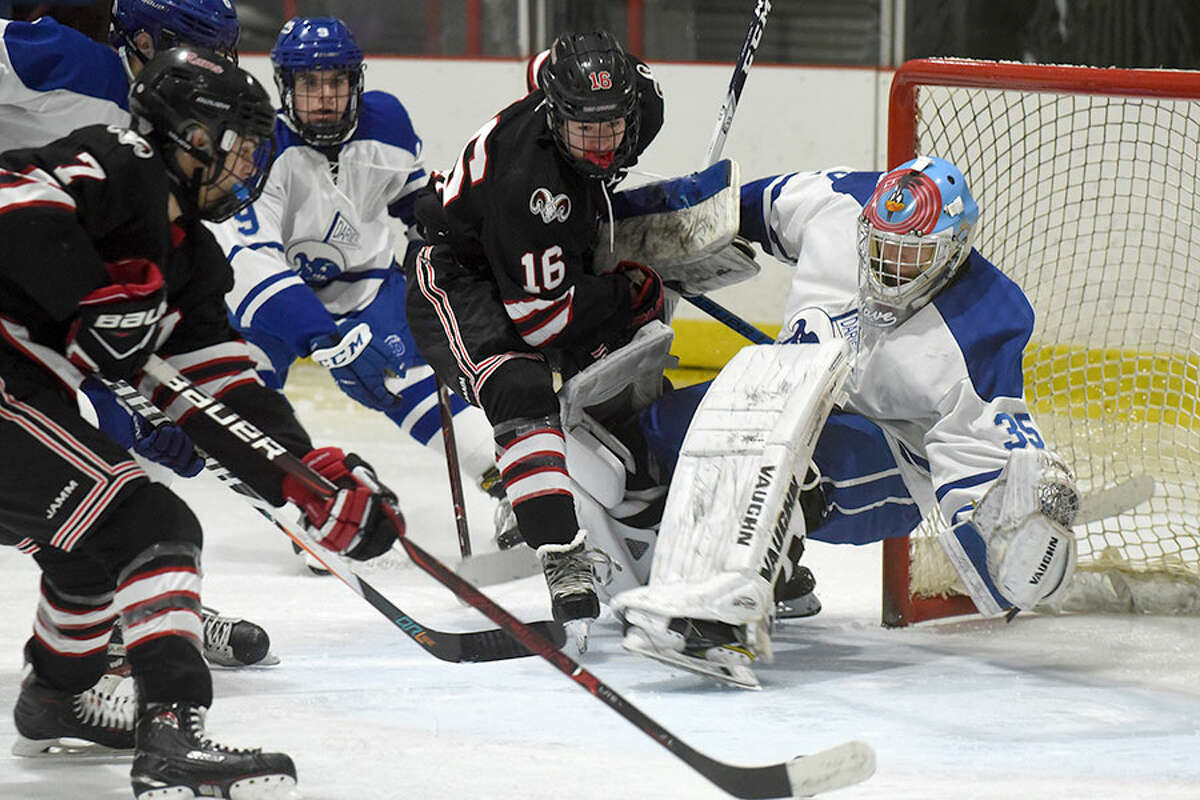 Darien goalie Henri Pfeifle dives back towards the puck while under attack from New Canaan's Campbell Lewis (16) and Brendan Knightly (7) during a boys ice hockey game at the Darien Ice House on Wednesday, Jan. 30. - Dave Stewart/Hearst Connecticut Media photo