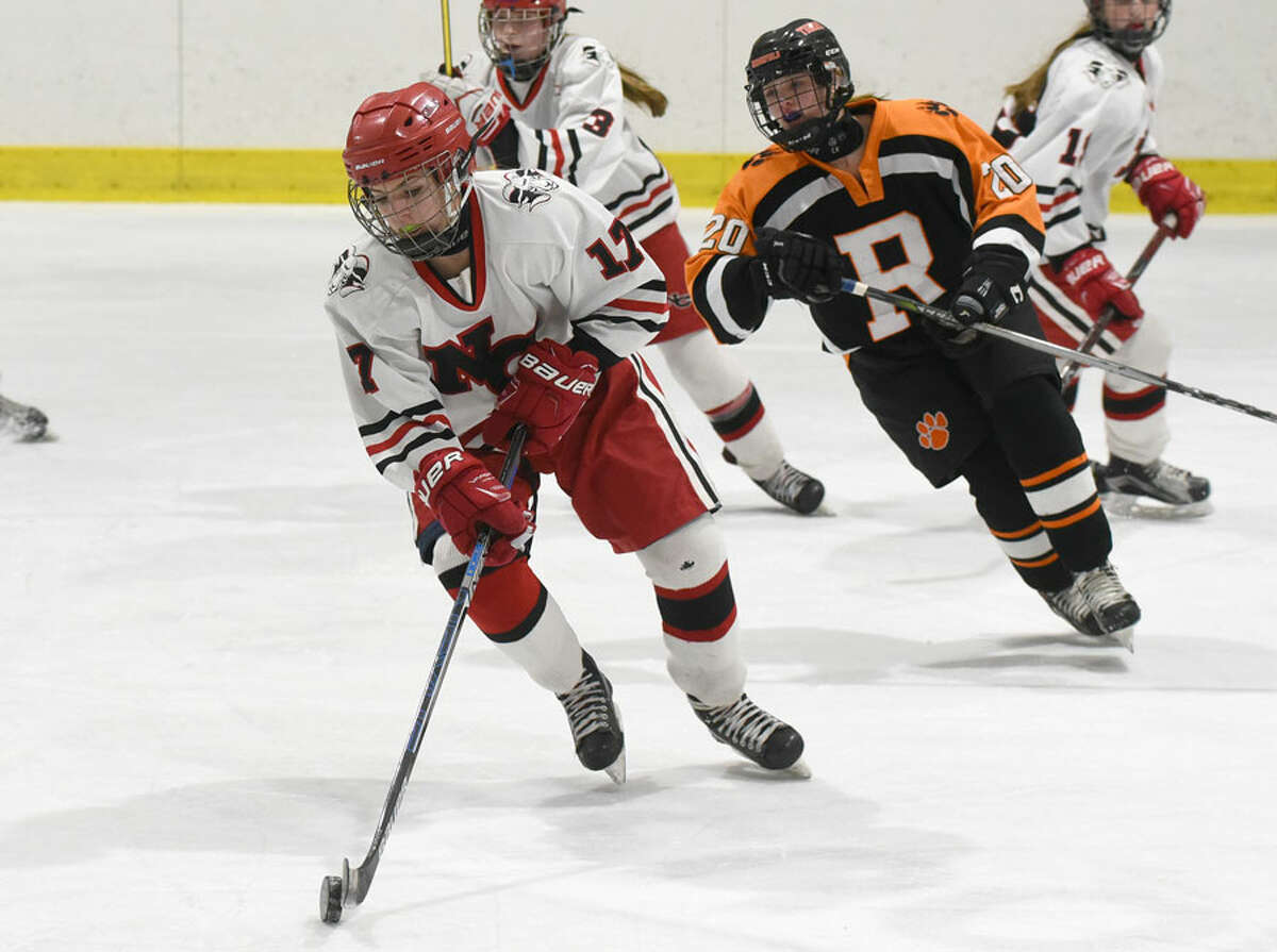 New Canaan's Sadie Frame (17) controls the puck in the neutral zone, as Ridgefield/Danbury's Rebecca Gartner during a girls ice hockey game at the Darien Ice House on Monday, Jan. 28. - Dave Stewart/Hearst Connecticut Media photo