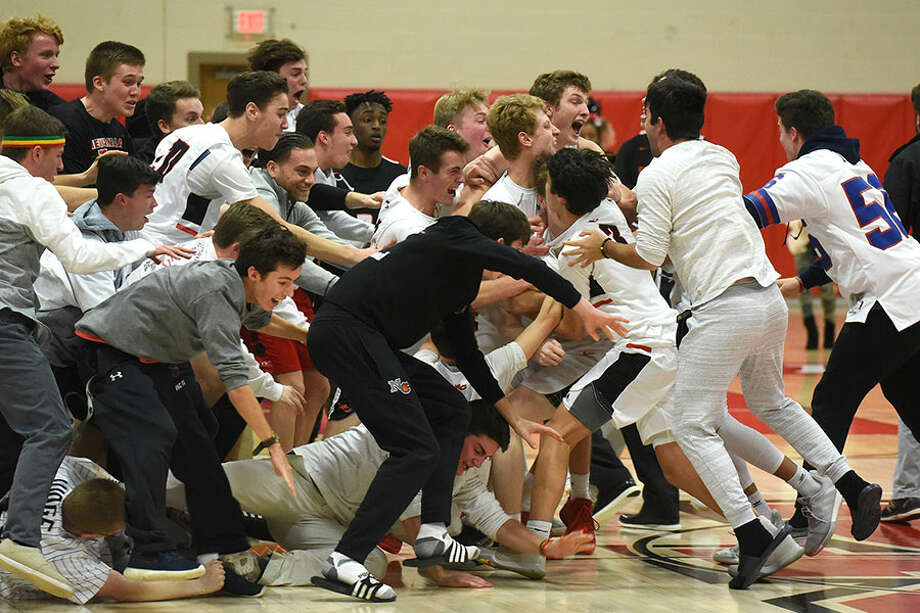 The New Canaan Rams and some of their fans celebrate on the court after the boys basketball team defeated Stamford 52-49 at New Canaan High School on Thursday, Jan. 10. — Dave Stewart/Hearst Connecticut Media photo