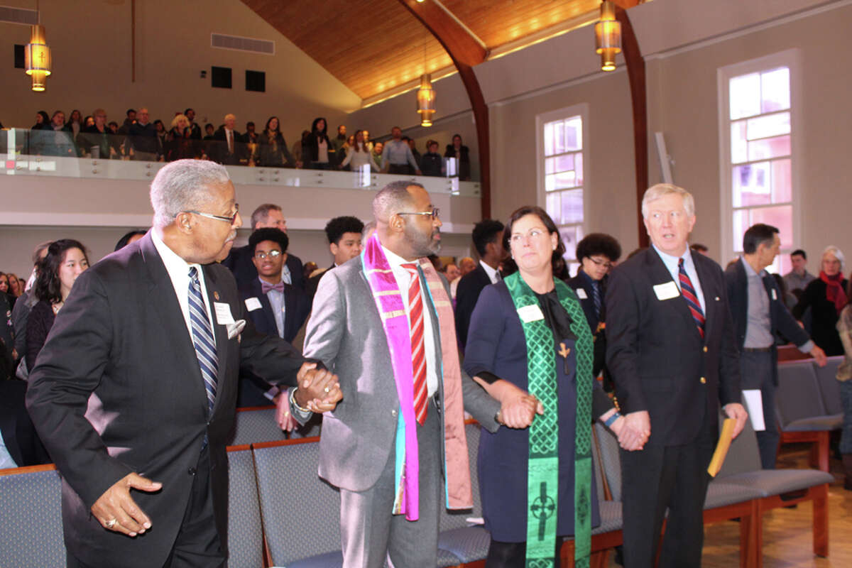 The Rev. Daniel Hickman Sr. of the Community Baptist Church, guest speaker the Rev. George Walker, the Rev. Kathryn Laird of the First Presbyterian Church and First Selectman Kevin Moynihan sing We Shall Overcome. -John Kovach photo