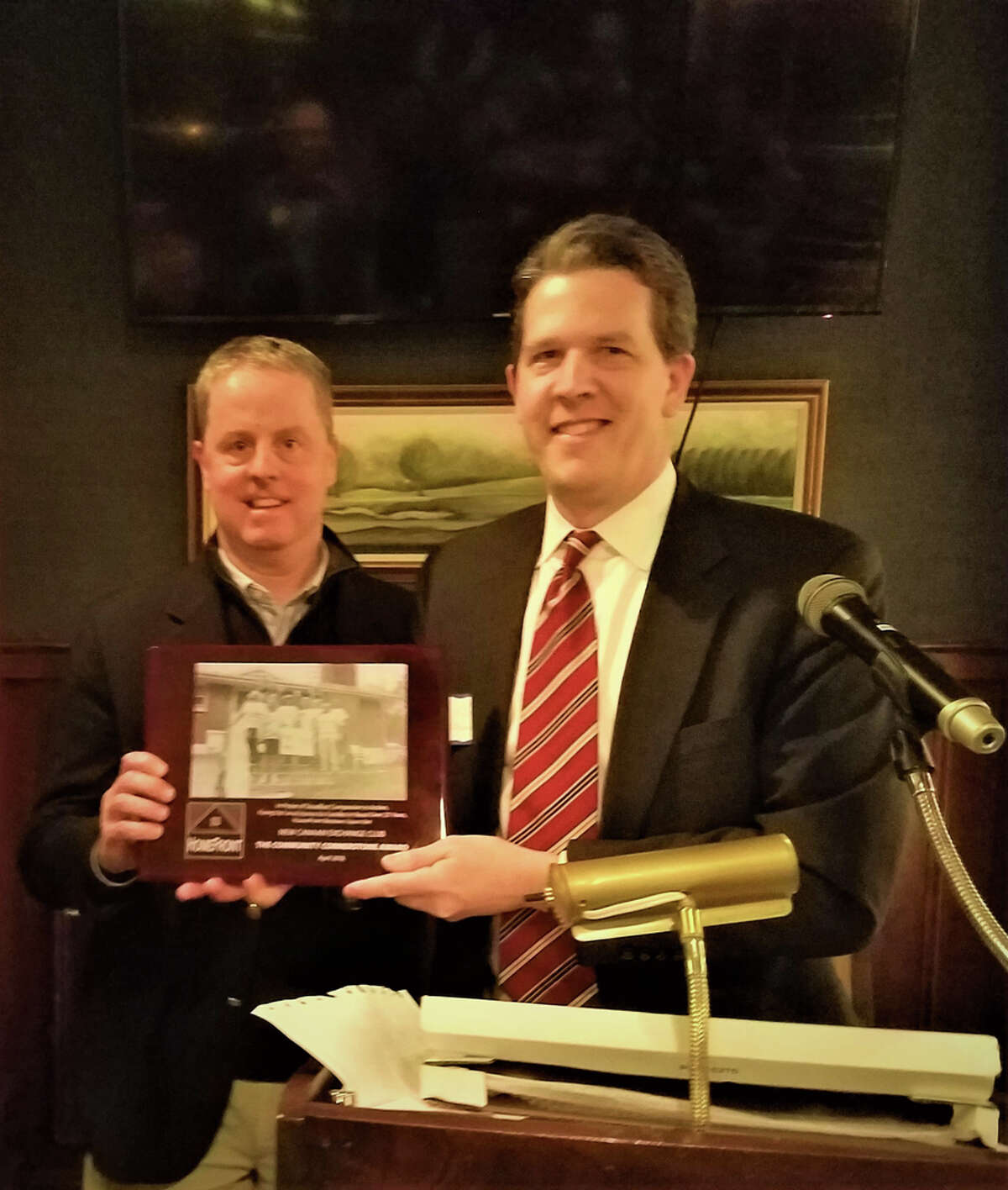 The Exchange Club of New Canaan has marked its 25th year by fixing homes. New Canaan Exchange Club President Jeff Platt and HomeFront Executive Director Sean O'Brien attend a club meeting where Platt presented the Community Cornerstone Award.
