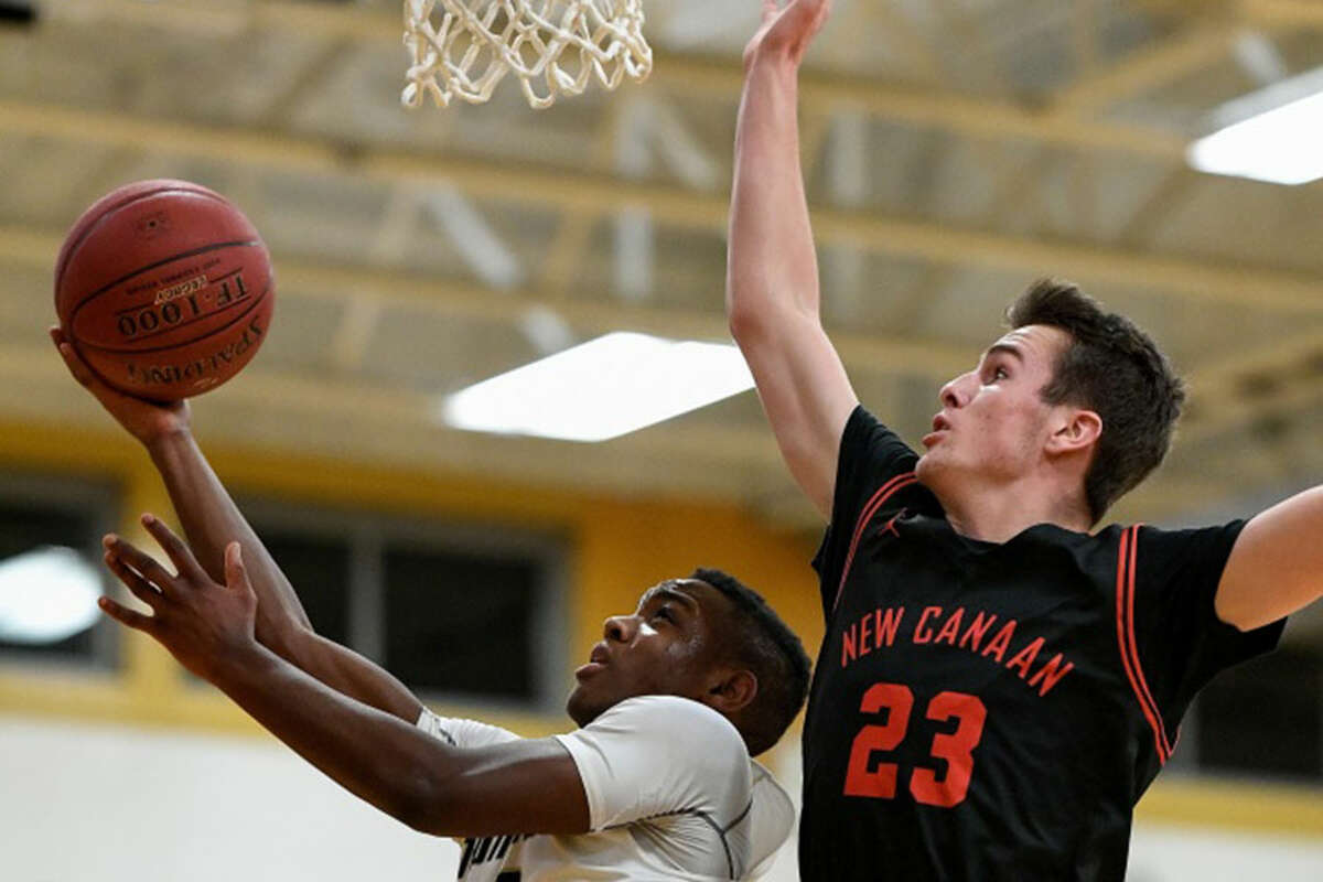 Trumbull's Mileeq Green (2) gets a shot off with New Canaan's Jack Richardson (23) defending. - David G. Whitham photo