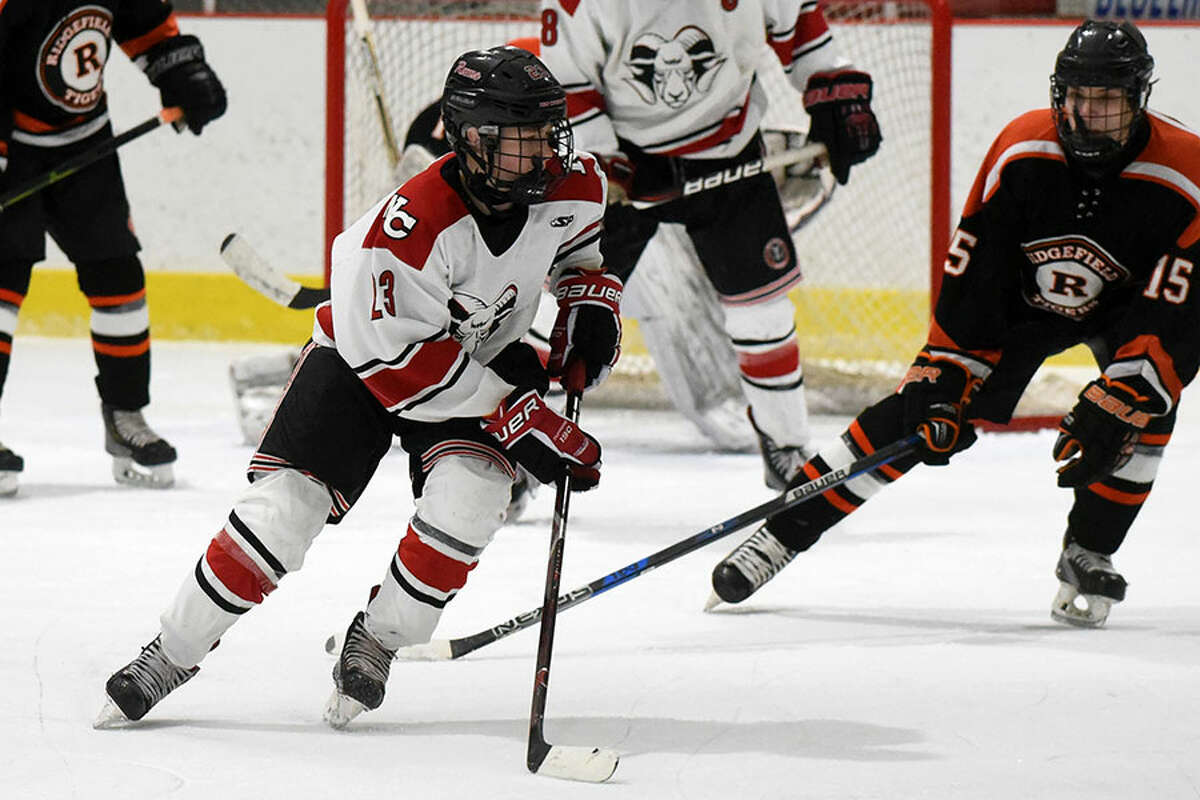 New Canaan's Boden Gammill controls the puck in the offensive zone during Tuesday night's boys ice hockey game against the Ridgefield at the Darien Ice House. - Dave Stewart/Hearst Connecticut Media photo