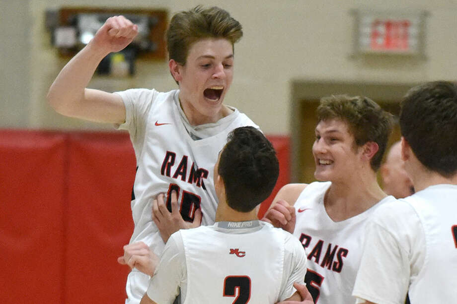 Ryan McAleer (10) and Alex Gibbens celebrate with Aaron Fishman (2) after Fishman hit three free throws to tie the score with 0.9 seconds remaining. — Dave Stewart/Hearst Connecticut Media photo