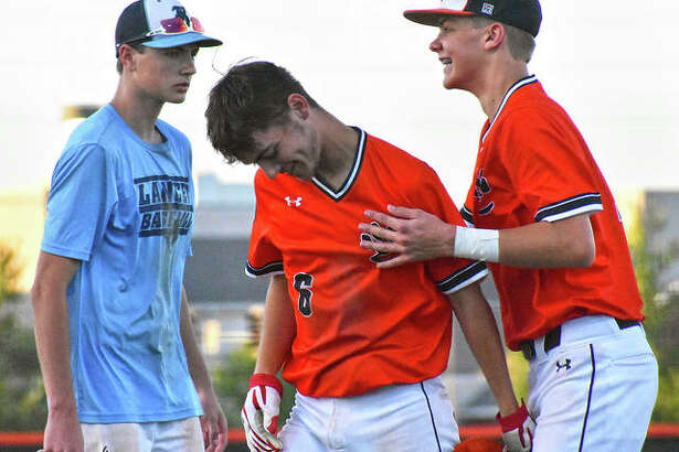Austin Segrest, center, is congratulated after his walk-off base hit in the seventh inning against Belleville East.