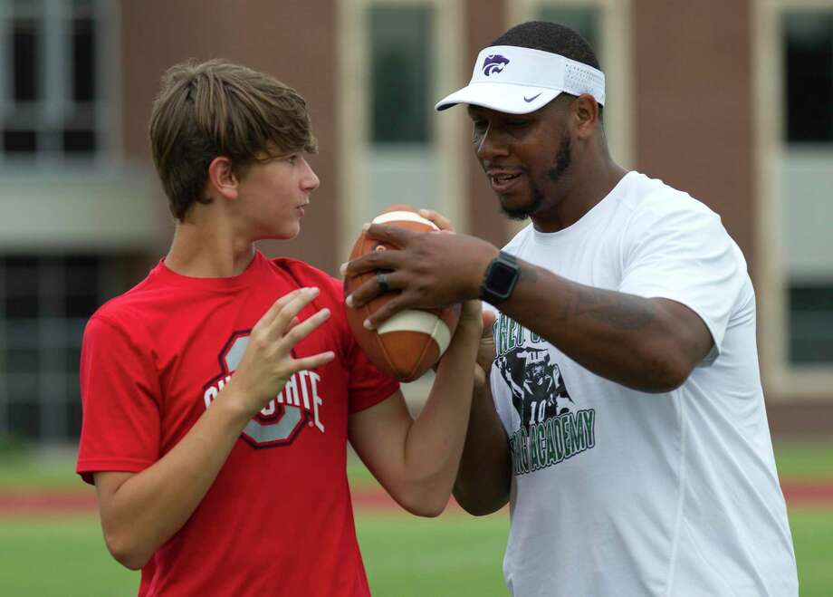 Former Kansas State Wildcat quarterback Michael Bishop works with Cooper Stone during the Piney Woods Passing Academy at Willis High School, June 25, 2019, in Willis. The camp is intended for incoming third graders through 12 graders and focused on stance, footwork, catching, running and other skills. Photo: Jason Fochtman, Houston Chronicle / Staff Photographer / Houston Chronicle
