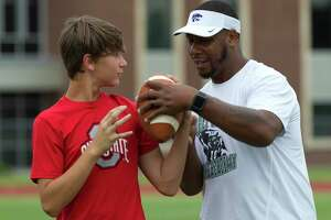 Former Kansas State Wildcat quarterback Michael Bishop works with Cooper Stone during the Piney Woods Passing Academy at Willis High School, June 25, 2019, in Willis. The camp is intended for incoming third graders through 12 graders and focused on stance, footwork, catching, running and other skills.