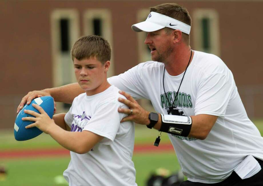 Willis head coach Michael Wall adjusts a camper's throwing motion during the Piney Woods Passing Academy at Willis High School, June 25, 2019, in Willis. The camp is intended for incoming third graders through 12 graders and focused on stance, footwork, catching, running and other skills. Photo: Jason Fochtman, Houston Chronicle / Staff Photographer / Houston Chronicle