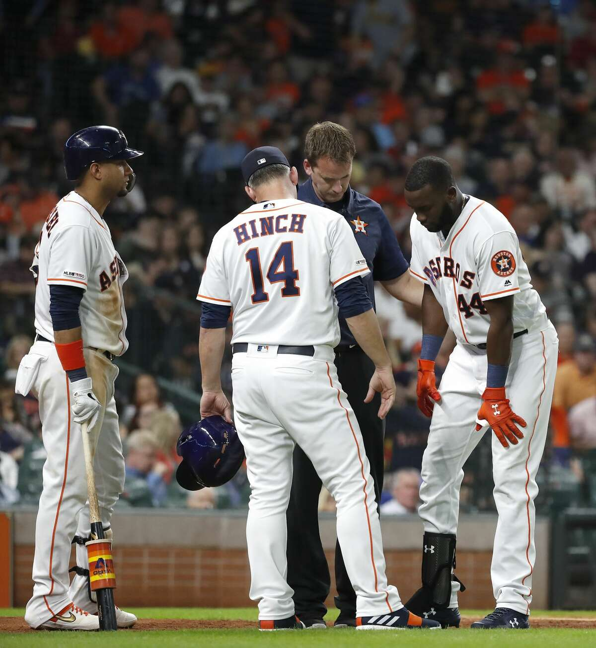 Houston Astros designated hitter Yordan Alvarez (44) is tended to after fouling a ball off his knee during the fourth inning of an MLB baseball game at Minute Maid Park, Tuesday, June 25, 2019.