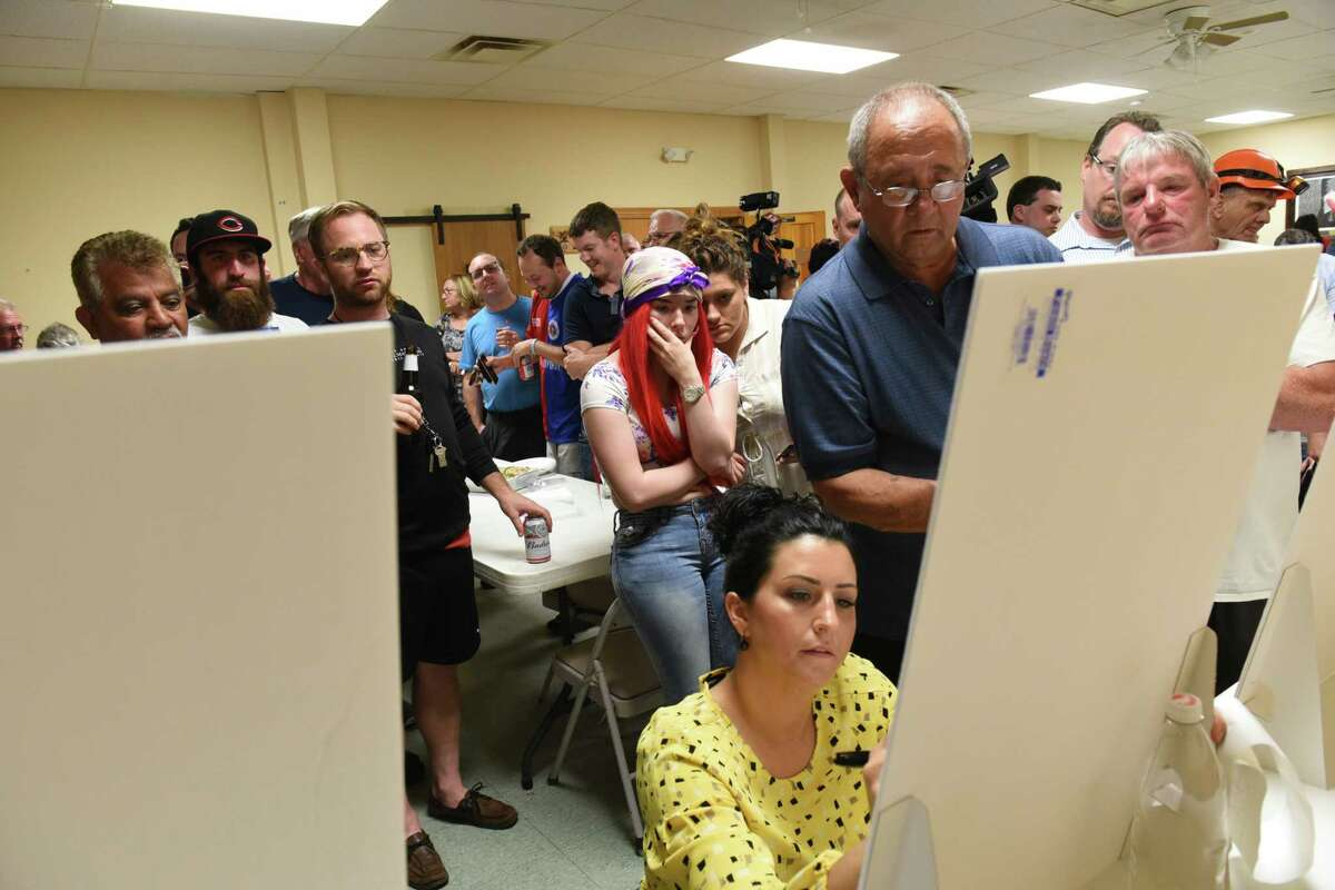 People at the Shawn Morse headquarters wait as Amanda Primeau writes down totals on white boards for the primary race for Cohoes Mayor at the Cohoes Legion Hall on Tuesday June 25, 2019 in Cohoes, N.Y. (Lori Van Buren/Times Union)