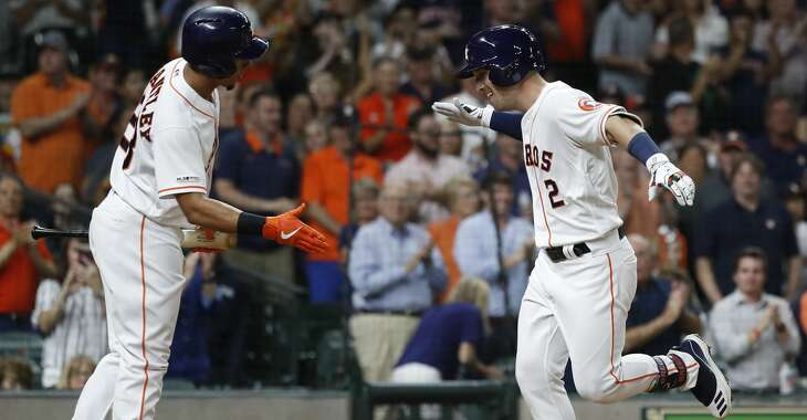 Houston Astros Alex Bregman (2) celebrates his home run with Michael Brantley (23) during the sixth inning of an MLB baseball game at Minute Maid Park, Tuesday, June 25, 2019.