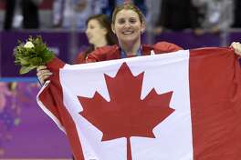 FILE - In this Feb. 21, 2014, file photo, Canada's Hayley Wickenheiser celebrates with the Canadian flag after beating the USA 3-2 in overtime at the Sochi Winter Olympics in Sochi, Russia. Wickenheiser is the Toronto Maple Leafs new assistant director of player development. (AP Photo/Paul Chiasson, The Canadian Press, File)