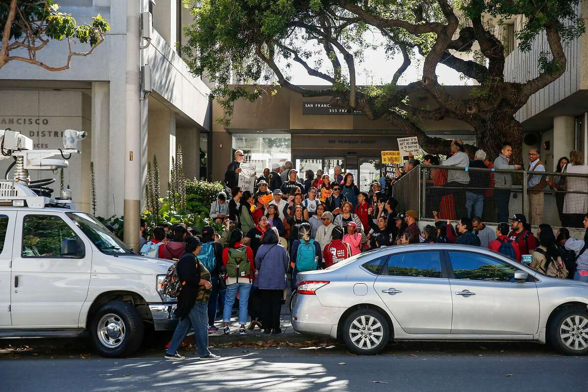 Protesters gather outside 555 Franklin before the San Francisco Unified School District school board meeting where the board discussed a controversial mural at George Washington High School Tuesday, June 25, 2019, in San Francisco, Calif.