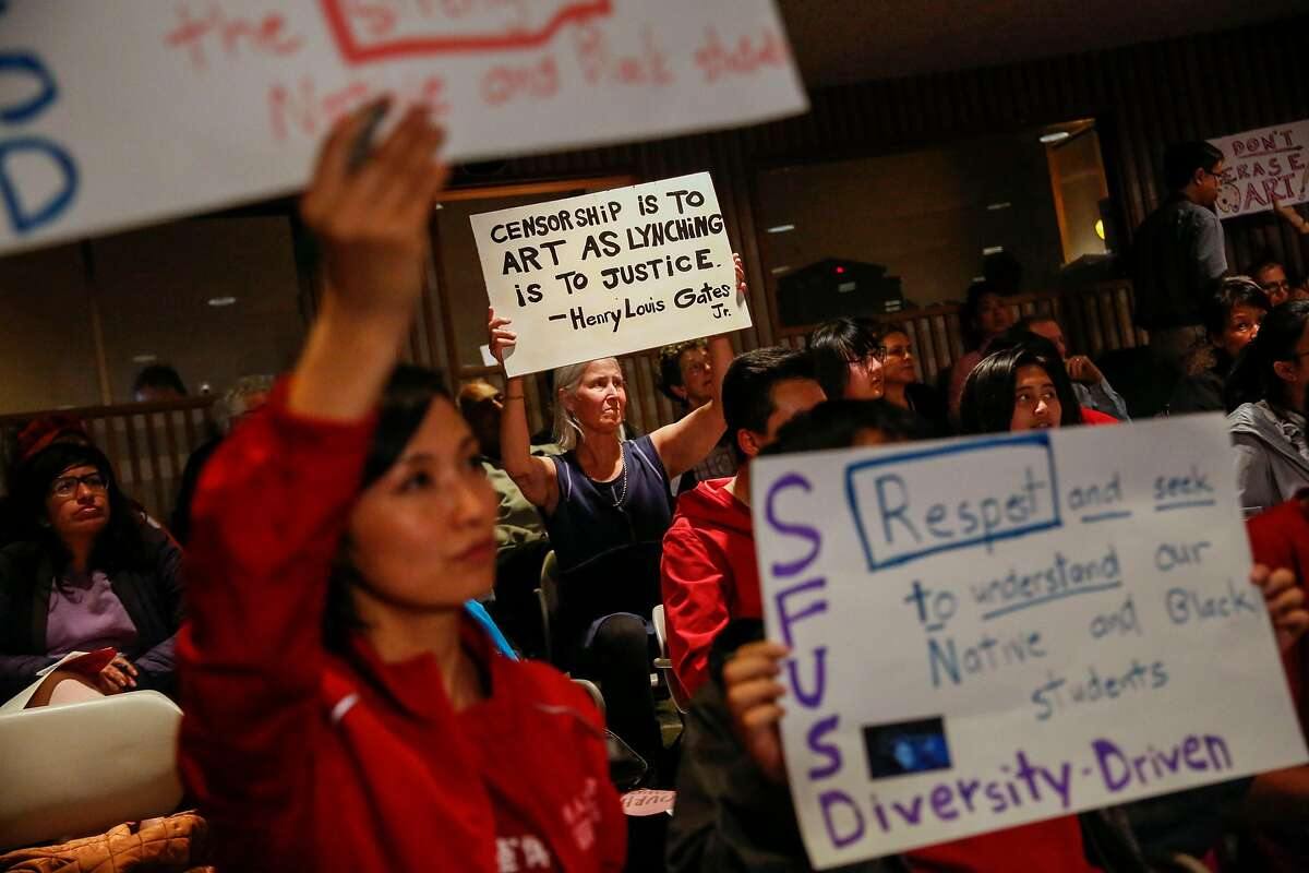 Carol Denney holds up a sign supporting controversial mural at George Washington High School during the San Francisco Unified School District school board meeting Tuesday, June 25, 2019, in San Francisco, Calif.