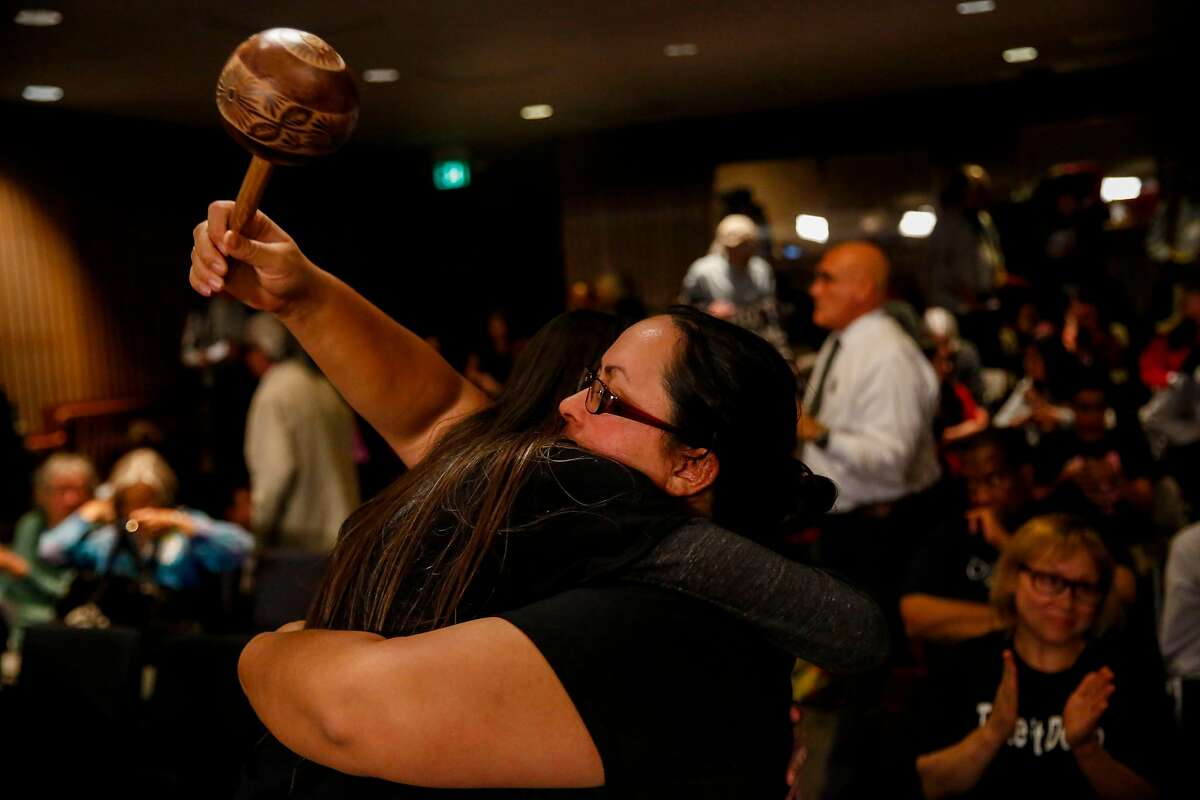 Mariposa de la Villaluna embraces Amy Anderson during the San Francisco Unified School District school board meeting where the board voted to remove or cover a controversial mural at George Washington High School Tuesday, June 25, 2019, in San Francisco, Calif.
