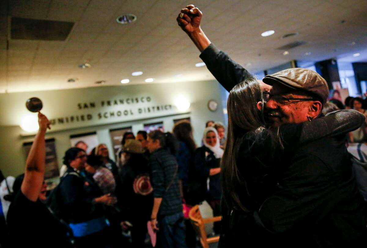 Norm Mattox raises a fist in the air as he embraces Amy Anderson during the San Francisco Unified School District school board meeting where the board voted to remove or cover a controversial mural at George Washington High School Tuesday, June 25, 2019, in San Francisco, Calif.