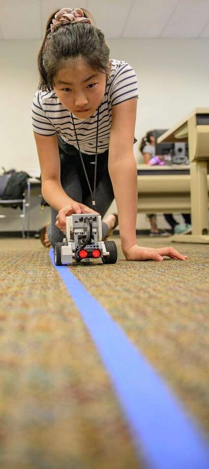 A student tests her robot's ability to follow a taped line during Camp Infinity. (Photo provided/Tim Inman, SVSU)