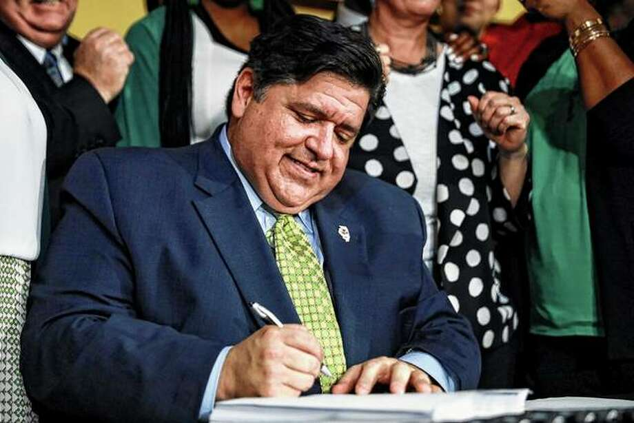 Gov. J. B. Pritzker signs a bill Tuesday that legalizes adult-use cannabis in Illinois, making Illinois the 11th state to do so. Photo: Amr Alfiky | Associated Press