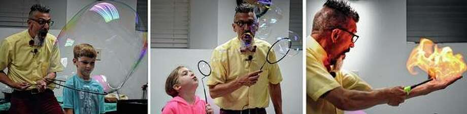 """Science takes a fun twist Tuesday as Absolute Science brought its hands-on program to Jacksonville Public Library. At left, """"Professor"""" Toto Johnson creates a bubble around Reid Hall, 8, the son of Christine and Brexton Hall. Izzy Vignone (center), 7, the daughter of Dallas and Monica Vignone, helps blow bubbles. At right, Professor Toto sets bubbles on fire in his hand as a part of the Absolute Science show."""