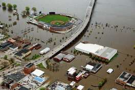 Modern Woodmen Park (top) and the surrounding downtown Davenport, Iowa, area are covered by Mississippi River floodwaters in early May. Prolonged flooding along the Mississippi River will cost more than $2 billion in repairs and cleanup, the Mississippi River Cities and Towns Initiative, and advocacy group for river communities, said Tuesday.