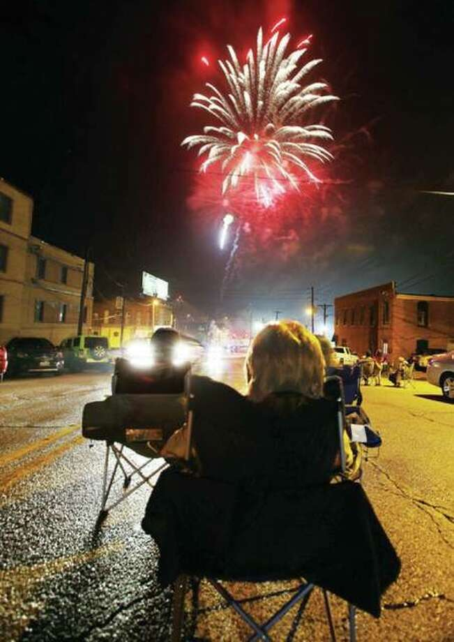 In this 2016 photo, people set up chairs in the middle of Henry Street in downtown Alton to watch the annual fireworks show. This year's event is set for July 3, despite riverfront damage left by flooding.
