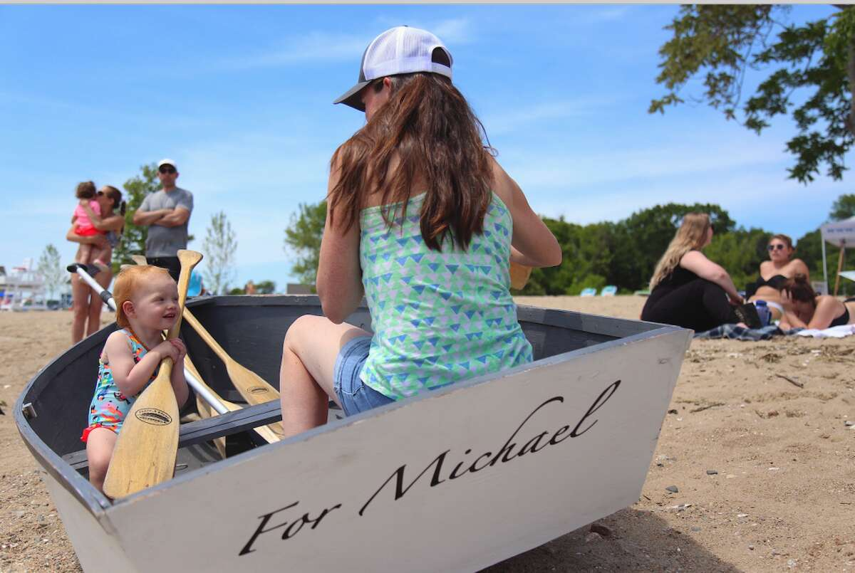 Jessica McKinney of Darien and her daughter Abigail, 2, enjoy a moment in the boat commemorating Michael Taylor at the 3rd annual Showdown on the Sound at Weed Beach on Saturday, June 8. - Jarret Liotta/Hearst Connecticut Media