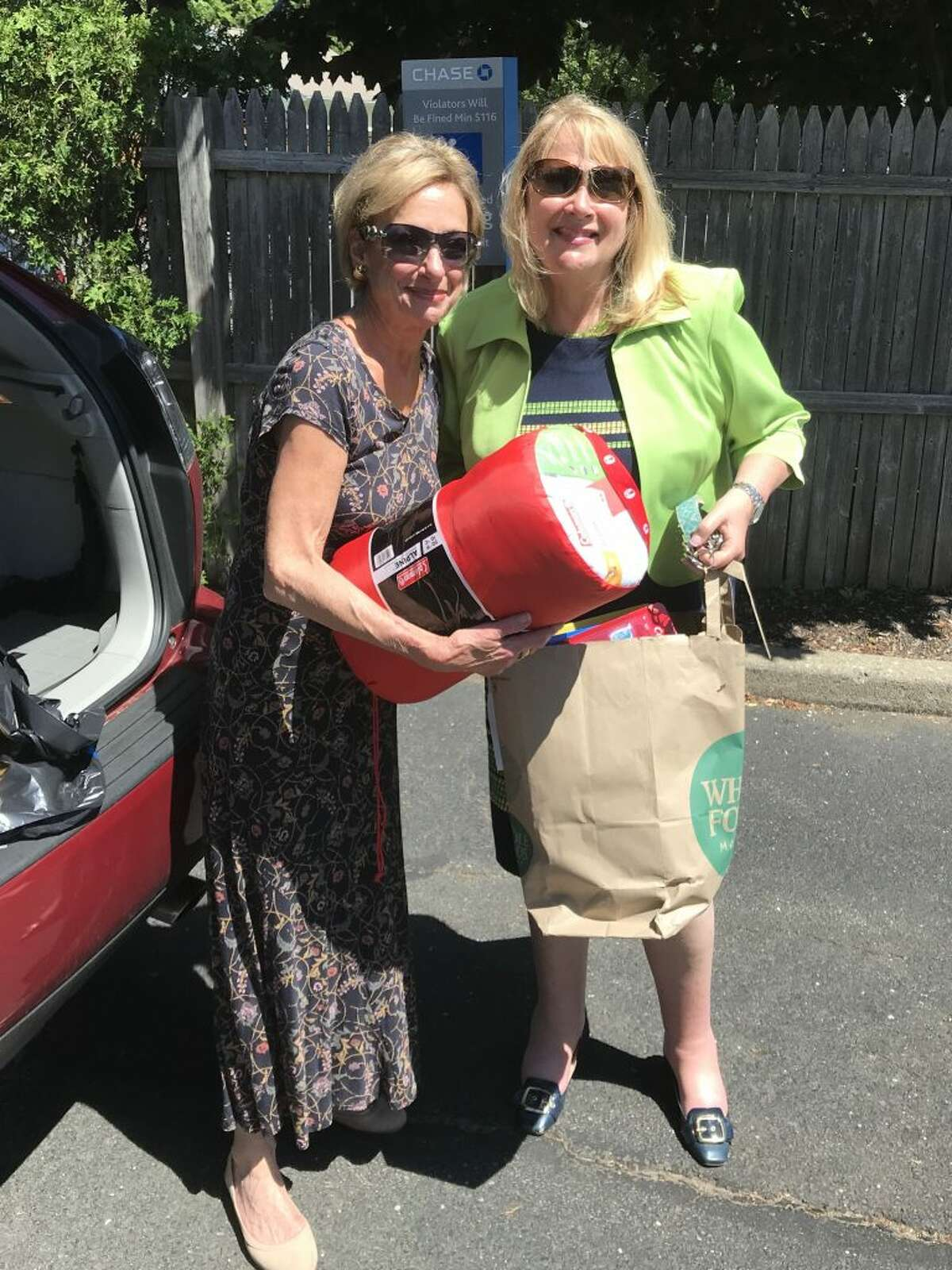Rita Bailey, left, executive director of the Darien Domestic Abuse Council, turning over bags of supplies to Deb Greenwood, right, executive director of the Center for Family Justice, to benefit kids going to Camp Hope America Connecticut.