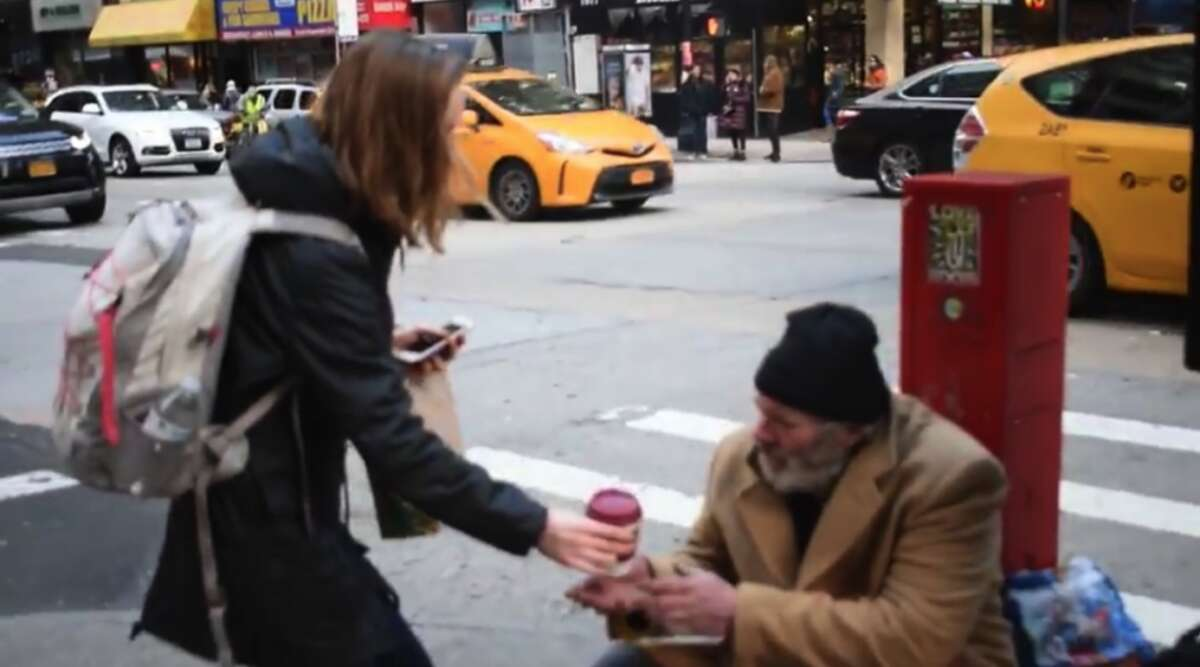 Kate Dempsey handing hot chocolate to a homeless man in New York City.