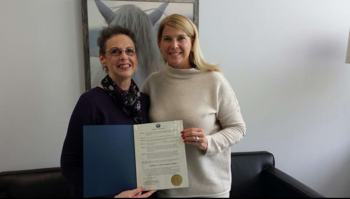 Robin Roscillo, a volunteer for the Alzheimer's Association, left,  picking up the Proclamation at Town Hall from First Selectman Jayme Stevenson.