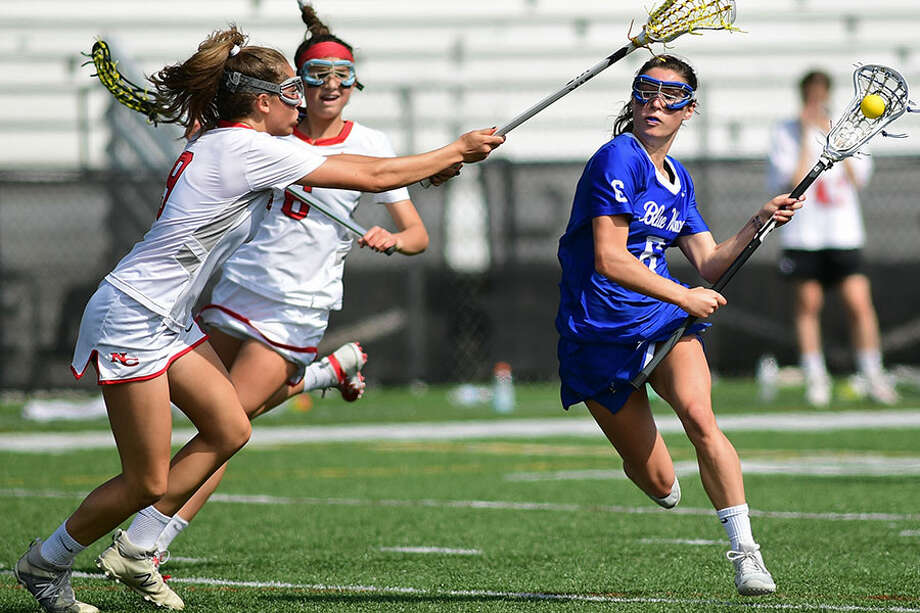 Darien's Katie Elders (6) drives as New Canaan's Katelyn Sparks (9) and Kaleigh Harden (6) defends during Saturday's girls lacrosse game at Dunning Field. — Eric Trautmann/Hearst Connecticut Media / Norwalk Hour