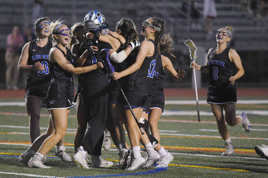 The Darien Blue Wave celebrates after defeating New Canaan 12-7 for the FCIAC girls lacrosse championship at Testa Field in Norwalk on Wednesday, May 22, 2019. — Dave Stewart/Hearst Connecticut Media / Hearst Connecticut Media
