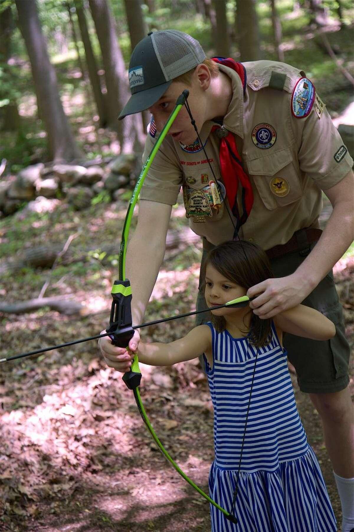 Boy Scout Frank Pirone, 15, of Darien, introduces Maren Papajohn, 4, of Darien, to archery.