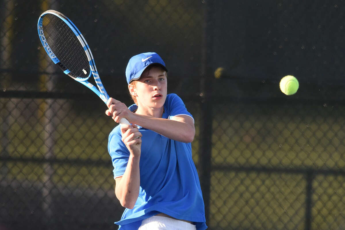 Darien's Nick Derby sends a backhand shot back over the net during the No. 3 singles match in the Wave's FCIAC semifinal contest at New Canaan on Thursday. - Dave Stewart/Hearst Connecticut Media