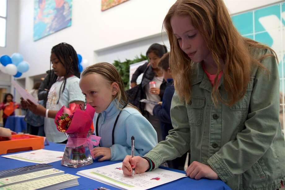 Sisters Elsa, 7, left, and Anna Keehlwetter, 10, of Darien, write down some observations at Healthy Kid Day on Saturday at the Darien YMCA.