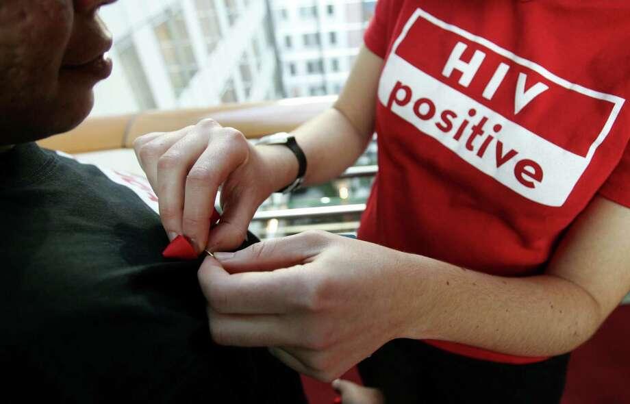 File photo of an AIDS activist pinning on a red ribbon. REUTERS/Francois Lenoir Photo: FRANCOIS LENOIR / REUTERS / X01164