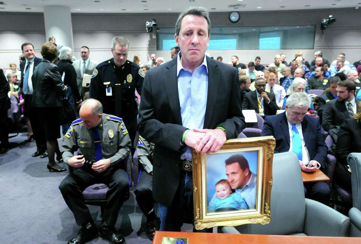Neil Heslin holding a photograph of himself with his son, Jesse Lewis, prepares to give testimony at a legislative hearing about gun control at the Legislative Office Building in Hartford in 2013.