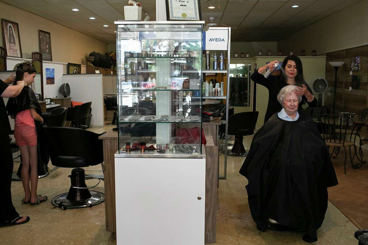 Mary Morales, owner of Vee's Hair and Spa, styles the hair of Adrienne Weynand, 91, while Serenity Moore, 11, left, has her hair cut by Megan Campbell at the salon.